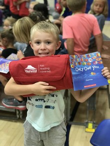 Sam Vere, grade one student at Raymond Elementary School, shows off his new book and reading blanket
